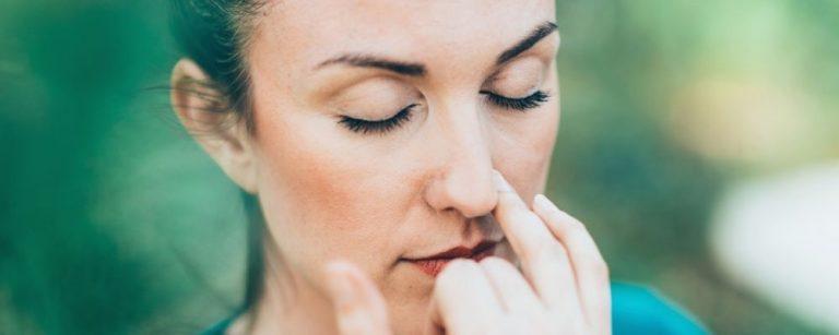 Vrouw met vinger tegen een neusgat en ademt rustig in