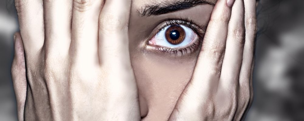 Vrouw die haar ene oog bedekt uit angst