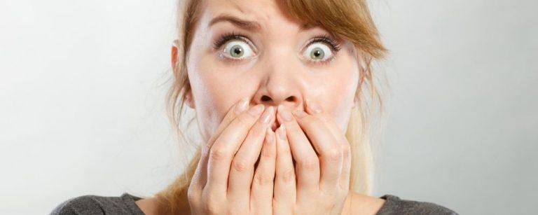 Vrouw mert angst en grote ogen en handen voor haar mond