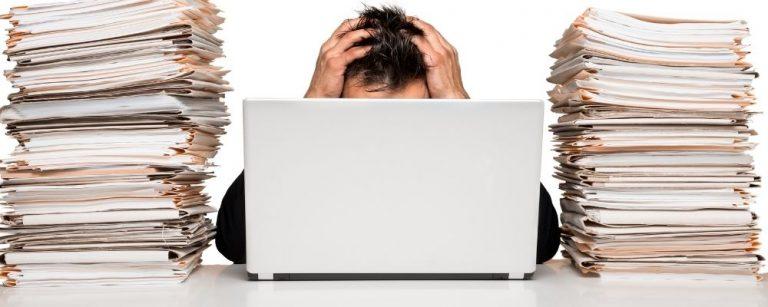 Man met handen in haren achter laptop met twee bergen aan werk naast hem