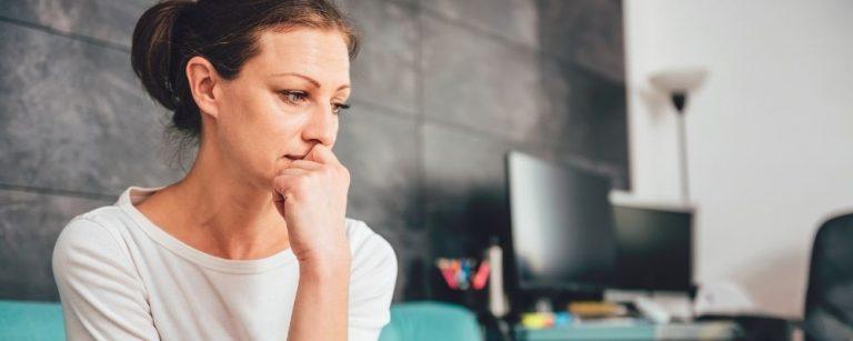 Vrouw met hand voor mond kijkt teleurgesteld voor zich uit