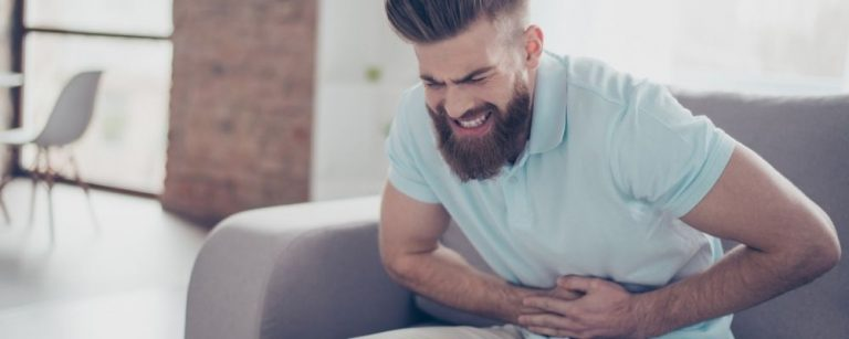 Man met buikpijn en handen op zijn buik door werkstress