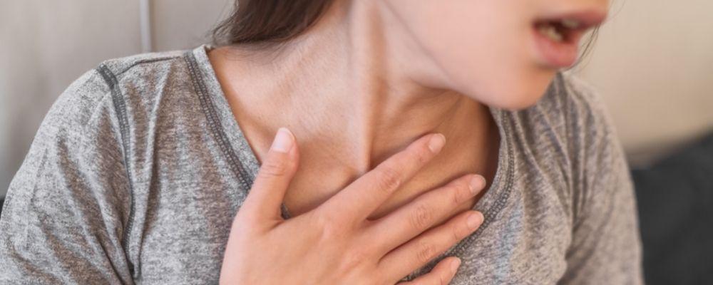 Vrouw ademt verkeerd met hand op borst