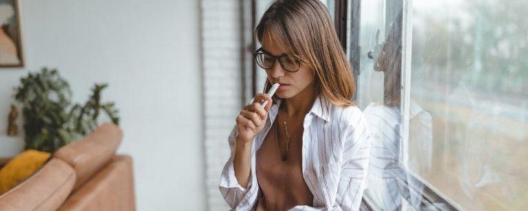 Vrouw met pen tegen haar mond denkt na over wat haar werkstress veroorzaakt
