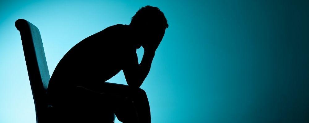 Silhouette van een depressieve man in een stoel