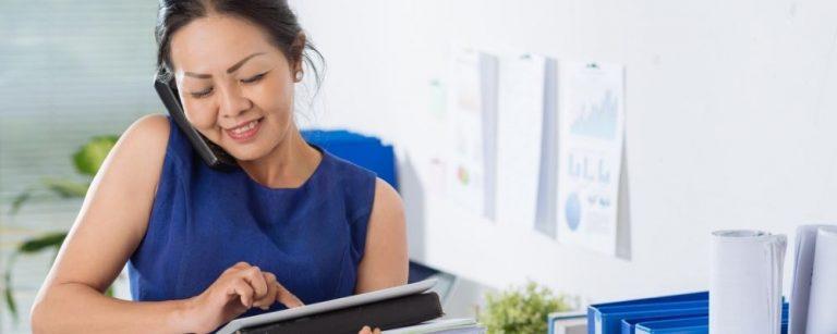 Werkende vrouw met telefoon aan oor en papier in hand