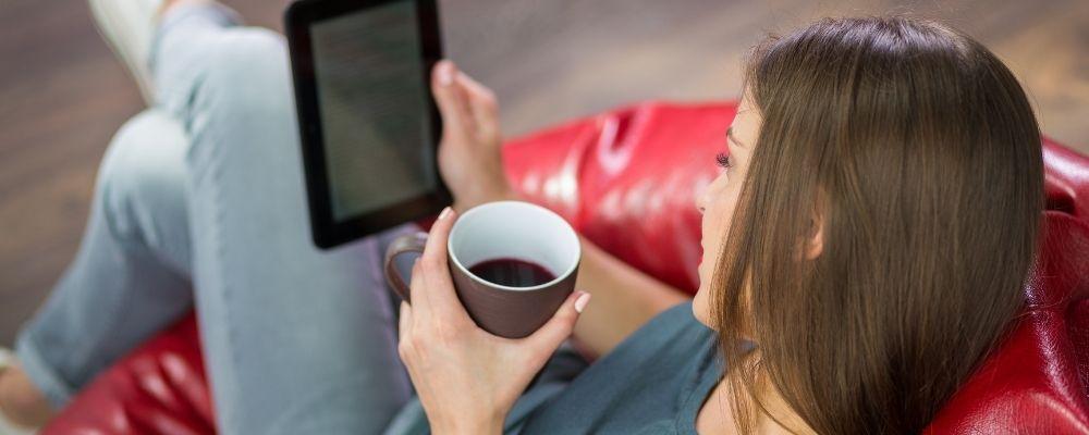 Vrouw zit op een stoel met koffie en leest een ebook