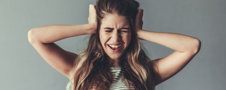 Vrouw schreeut en houdt haar hoofd vast