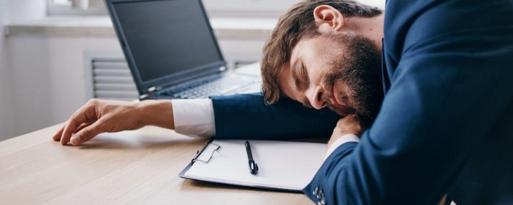 Vermoeide man slaapt op zijn laptop