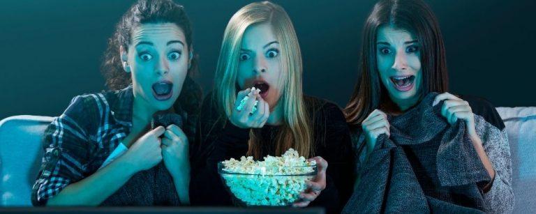 Drie meiden kijken samen een film en eten popcorn