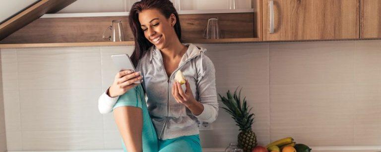 Vrouw zit op aanrecht en eet een appel in sportkleding