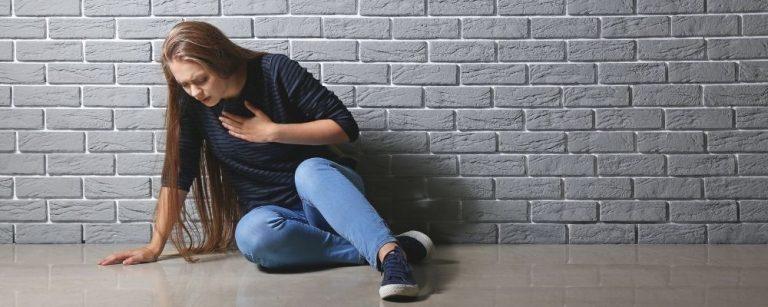 Vrouw zit op de grond met hand op haar borst door hyperventilatie