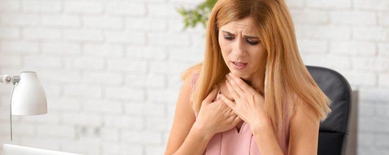 Vrouw met handen bij haar keel door hyperventilatie