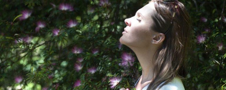 Vrouw loopt door tuin heen en ademt rustig