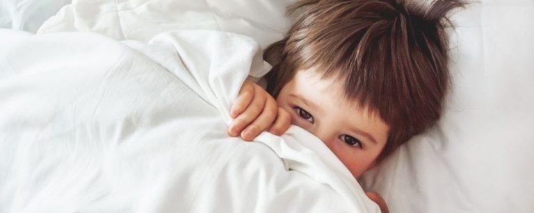 Kind ligt wakker in bed
