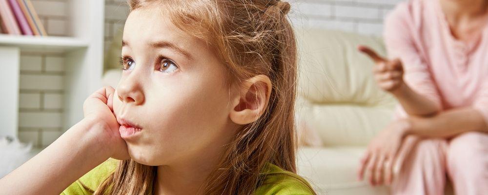 Kind kijkt weg van haar moeder en onderdrukt haar woede