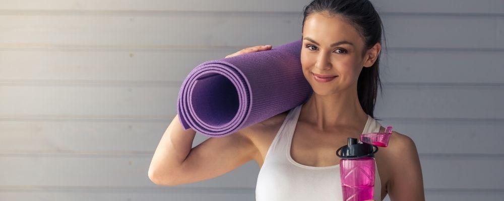 Sportende vrouw met een matje op haar schouder en een waterfles in haar hand