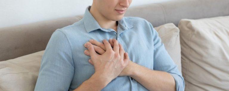 Man met handen op zijn pijnlijke borst