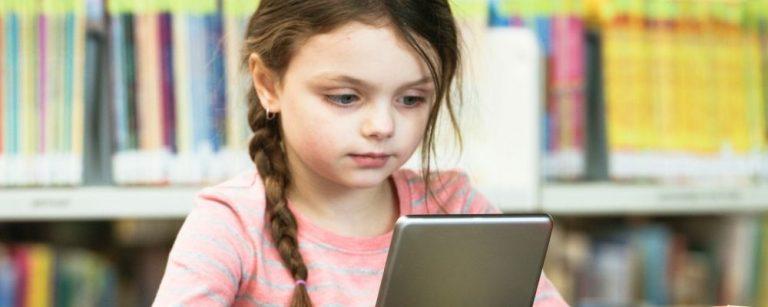 Nieuwsgierig meisje wil leren en kijkt naar tablet