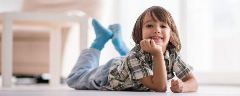 Jongentje ligt thuis op de vloer