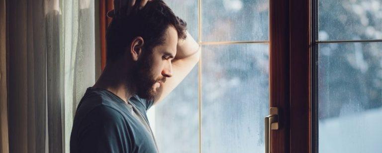 Man kijkt uit het raam en denkt na met hand op zijn hoofd