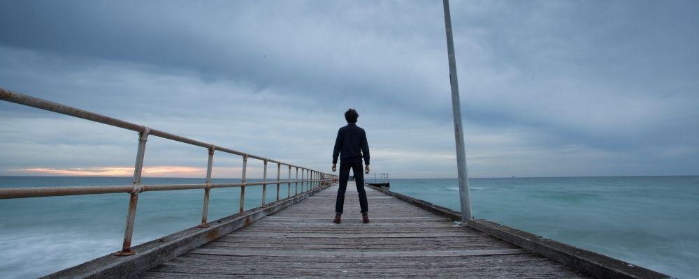 Man staat helemaal alleen op een pier