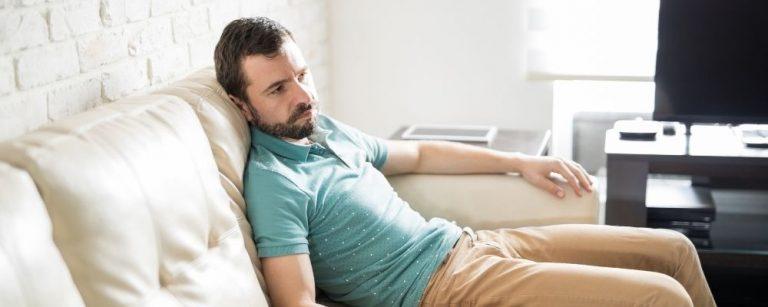 Apatische man zit verveeld op de bank door overspanning