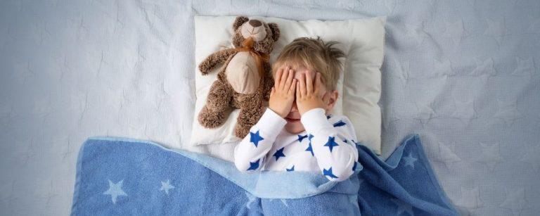 Jongetje in bed met handen op ogen