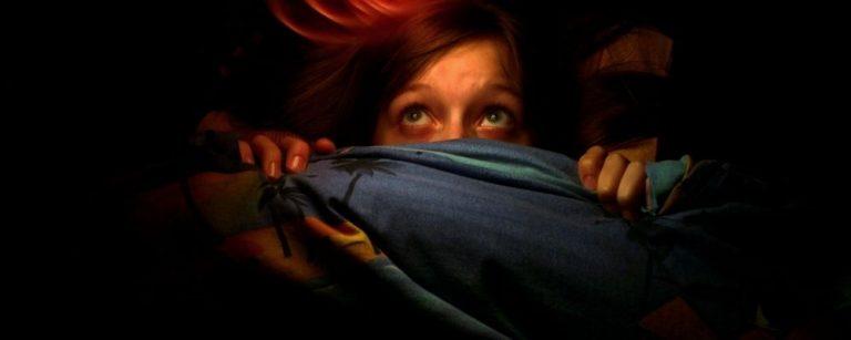 Vrouw ligt met angst onder de dekens verstopt