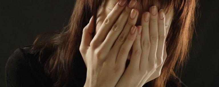 Vrouw bedekt haar gezicht met beide handen uit angst