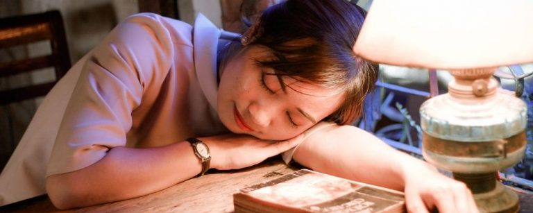 Overspannen vrouw ligt uitgeput op haar bureau met haar hoofd op haar arm