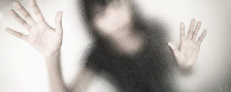 Vrouw achter glas met haar handen tegen het glas aan