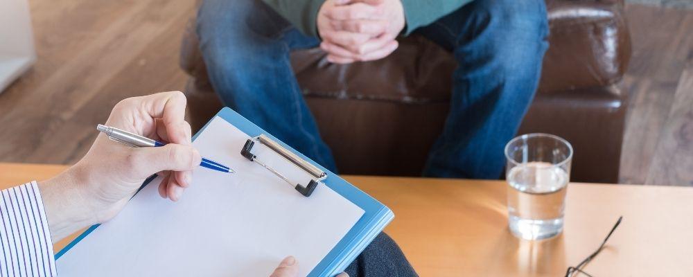 Man zittend op een stoel bij een psychotherapeut