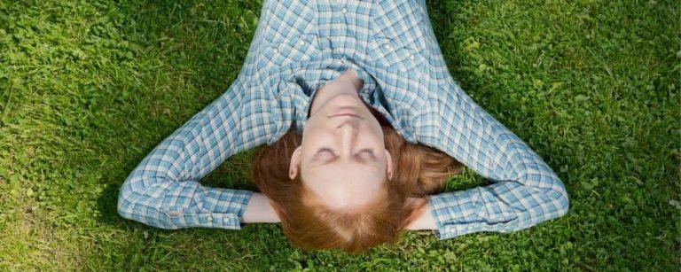 Relaxende vrouw ligt met gesloten ogen op het gras