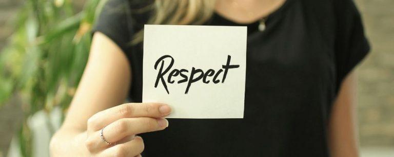 Vrouw houdt papier vast waarop respect staat