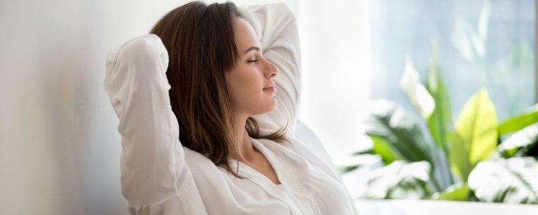 Vrouw zit op de bank met haar handen achter haar hoofd en ademt rustig in
