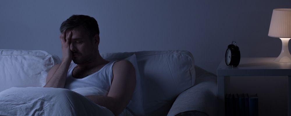 Man ligt wakker in bed en heeft hand tegen zijn voorhoofd