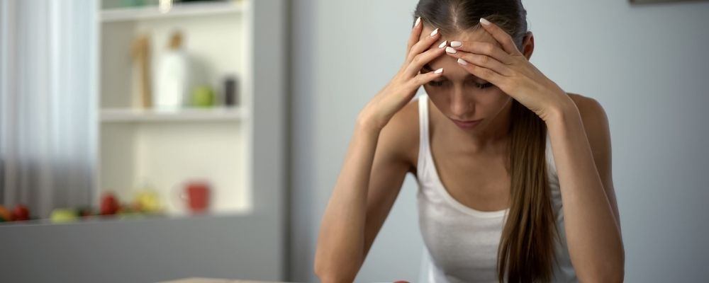 Vrouw heeft handen op haar voorhoofd en voelt zich suf