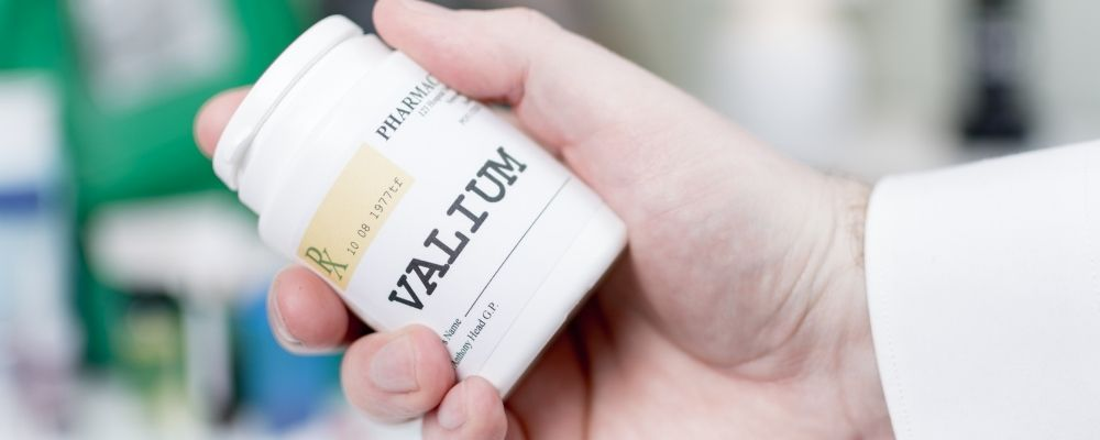 Man met een potje Valium in zijn hand