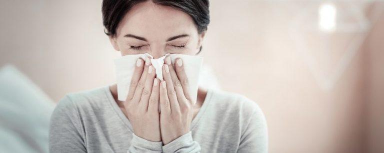 Verkouden vrouw die in een tissue haar neus snuit