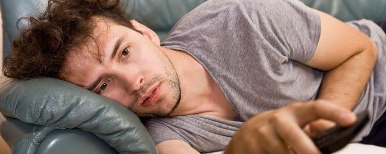 Man ligt lui op bank tv te kijken
