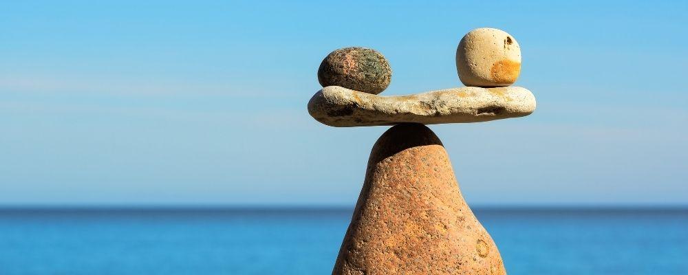Twee stenen balanceren op een andere steen