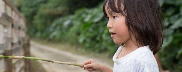 Kind buiten aan het spelen met een takje