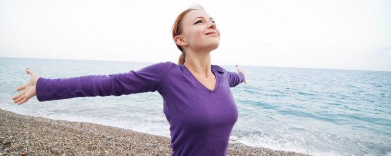 Vrouw die haar armen spreidt en over het strand loopt