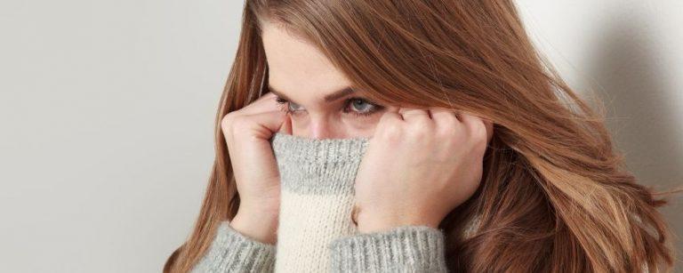 Vrouw trekt trui over haar neus heen uit paniek