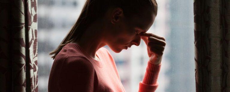 Vrouw met chronische stress die haar voorhoofdsbeen vasthoudt