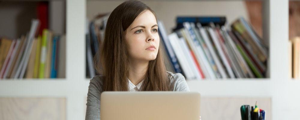 Vrouw kan zich niet concentreren en kijkt weg van haar laptop