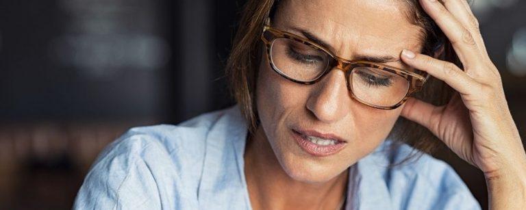 Vrouw die gestresst is met hand tegen de zijkant van haar hoofd