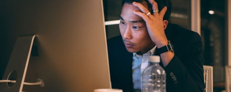 Man met werkstress achter de pc met hand tegen zijn hoofd