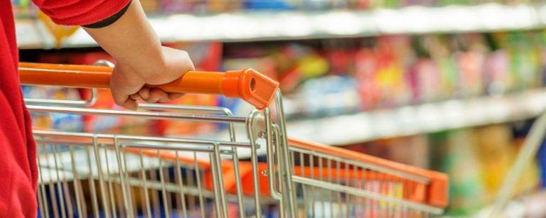 Persoon duwt een winkelwagen door de supermarkt
